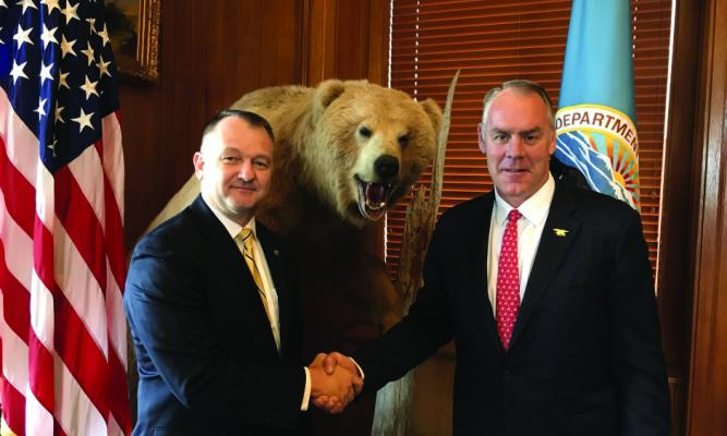Interior Secretary Ryan Zinke (right) welcomes incoming YNP Superintendent Cam Sholly while a stuffed Yogi doesn't appear too happy about it.