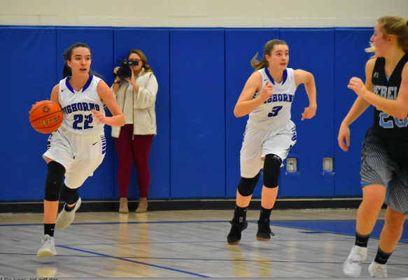 "Emma Flach dribbles down the court. The 5'7"" junior brought in 12 points during the December 20 home game, the most of any player on the team."