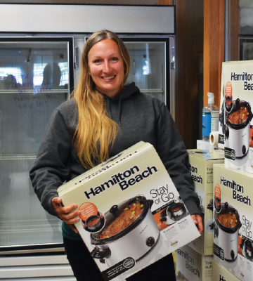 Sarah Gaither, operations manager for the Big Sky Community Food Bank shows one of the many crock pot options available to residents who need them. PHOTO BY JANA BOUNDS