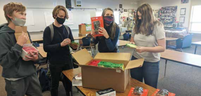 (L to R) 9th graders Max Woodger, Simon Gough, Dr. Kate Eisele and Greta McClain open the STEM kit they received from the Society for Science & the Public. PHOTO COURTESY KATE EISELE