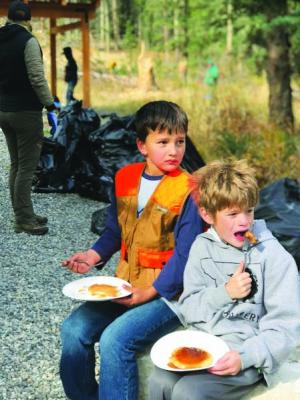 Elijah Harder (left) and Wyatt Cohen enjoy pancakes slathered in maple syrup after a morning of community service and camaraderie at Big Sky's shooting range.