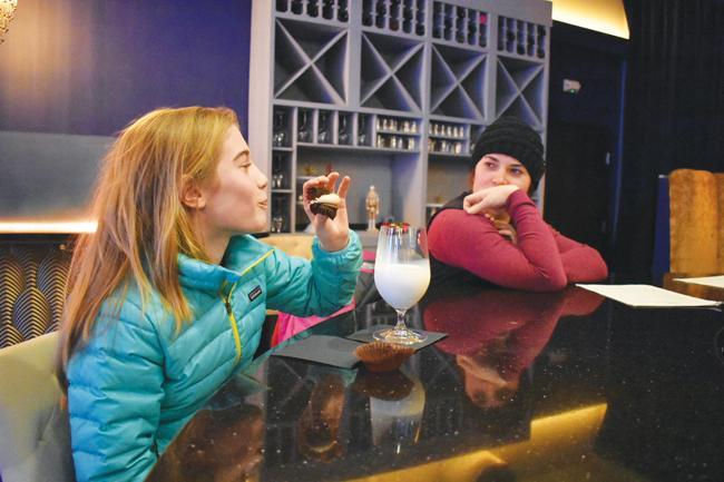 An ice-cold glass of vanilla-laced milk from the tap and a chocolate cupcake compliment a day on the slopes for Bryn Welty, seated with Anna Mckay (right).