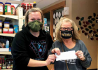 Gina Dee (R) who has been teaching local children art and created an art show at The Rocks to auction off their work to benefit Big Sky Community Food Bank drops off a $6,000 check to the food bank's Operations Manager & Service Navigator Sarah Gaither Bivens. PHOTO BY JANA BOUNDS